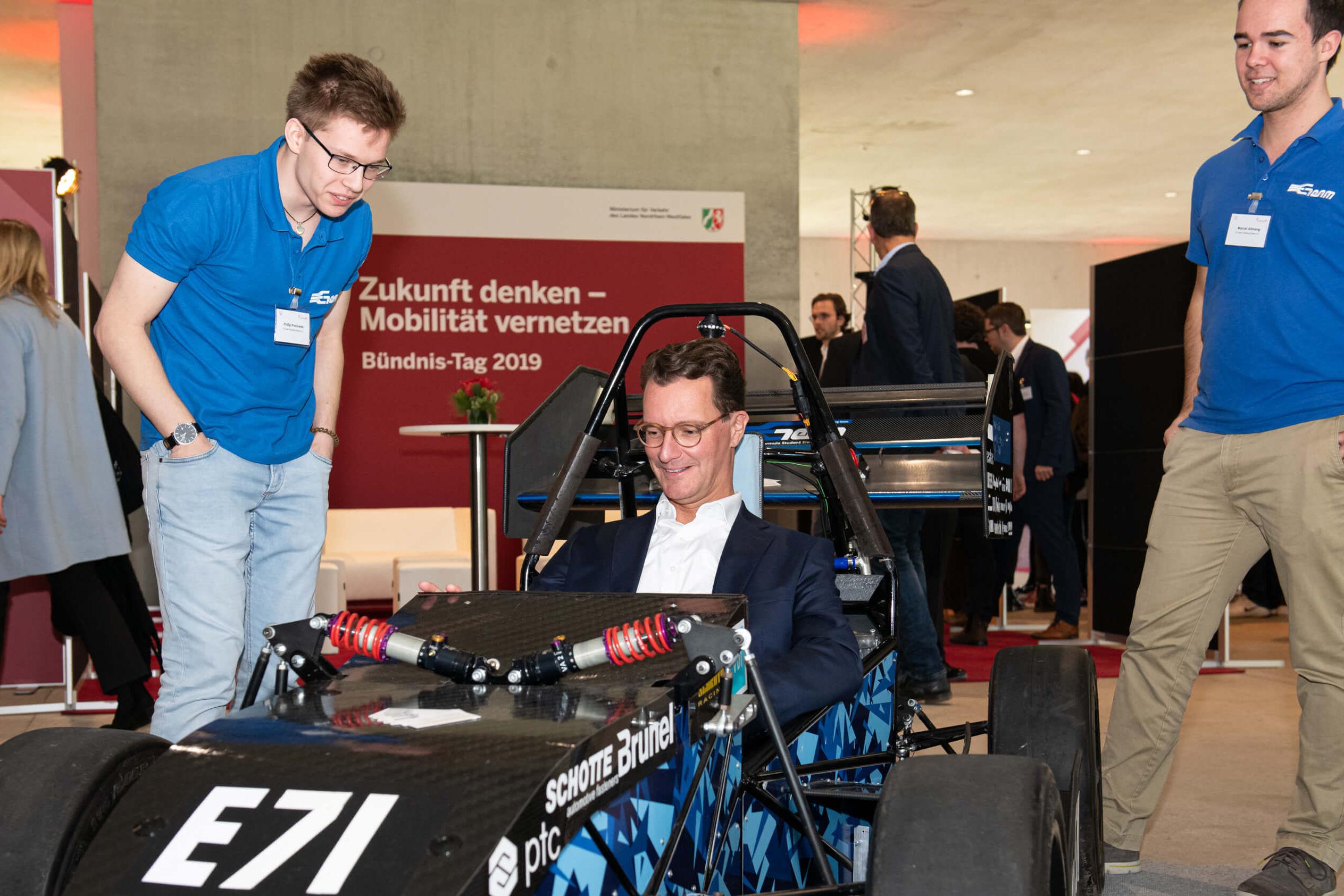 Der Verkehrminister NRW, dunkle Haare und dunkler Angug, sitzt in einem futuristischen Gefährt. Zwei junge Männer mit Namensschildern stehen daneben.