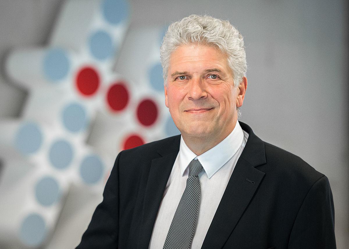 Portraitfoto von Stephan Heuschen: Weisshaariger Mann, lächelnd, in Anzug, Hemd und Krawatte