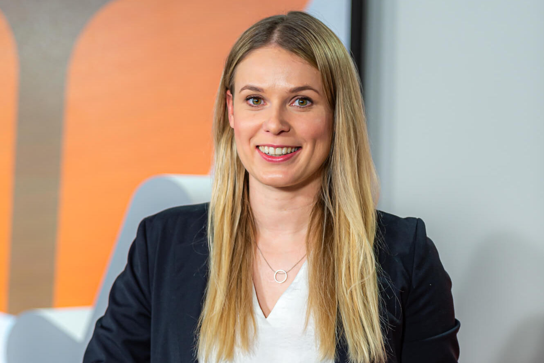 Blonde junge Frau mit Moderationskarten in Businesskostüm.