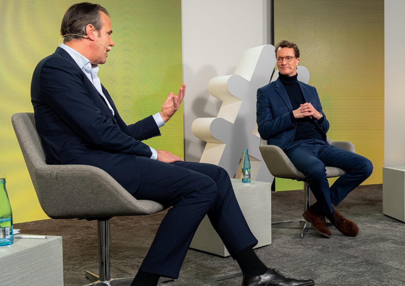 Zwei Männer mit dunklen und ein Mann mit hellen Haaren und dunklen Anzügen sitzen in einem Studio und unterhalten sich.