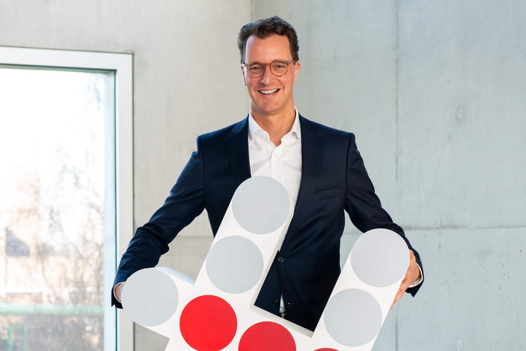 Verkehrsminister NRW, dunkelhaariger Mann mit dunklem Anzug, hält die Logo-Raute von Bündnis für Mobilität und lächelt in die Kamera.
