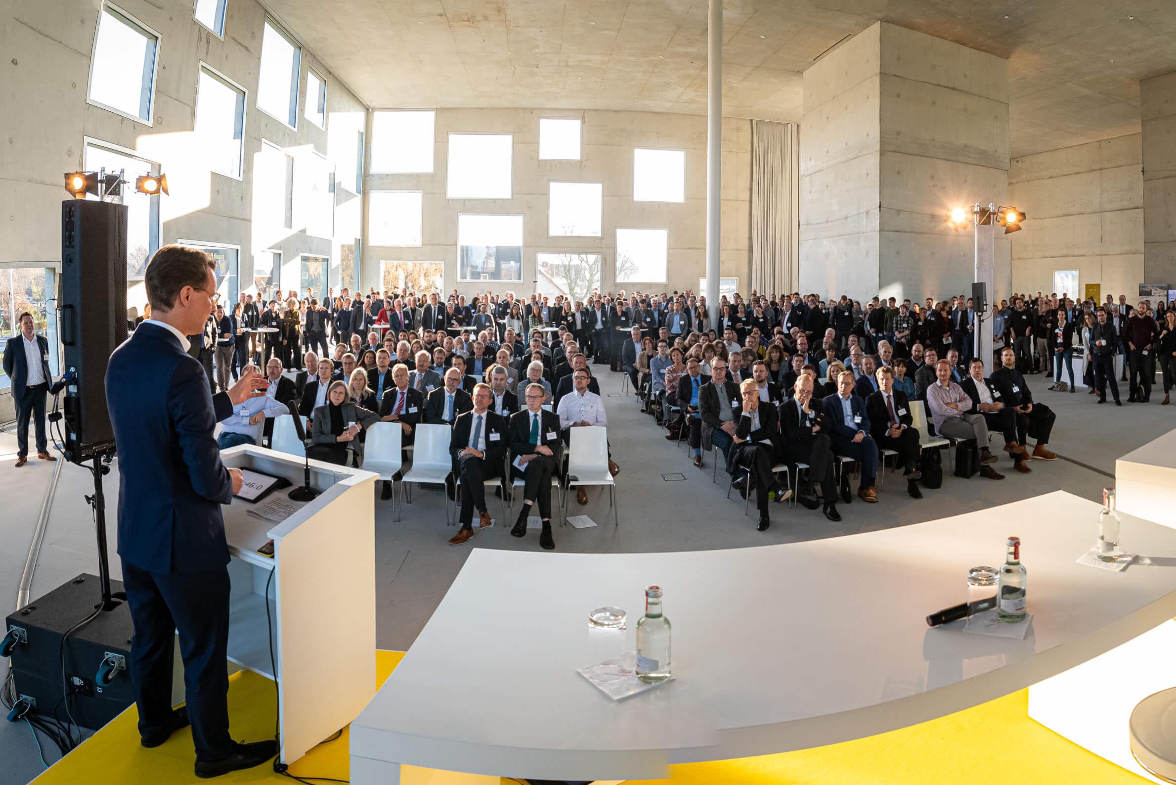 Verkehrsminister Wüst, dunkelhaariger Mann in dunklem Anzug steht auf einer Bühne an einem Rednerpult und spricht zu einem großen Publikum in einem großen Gebäude.