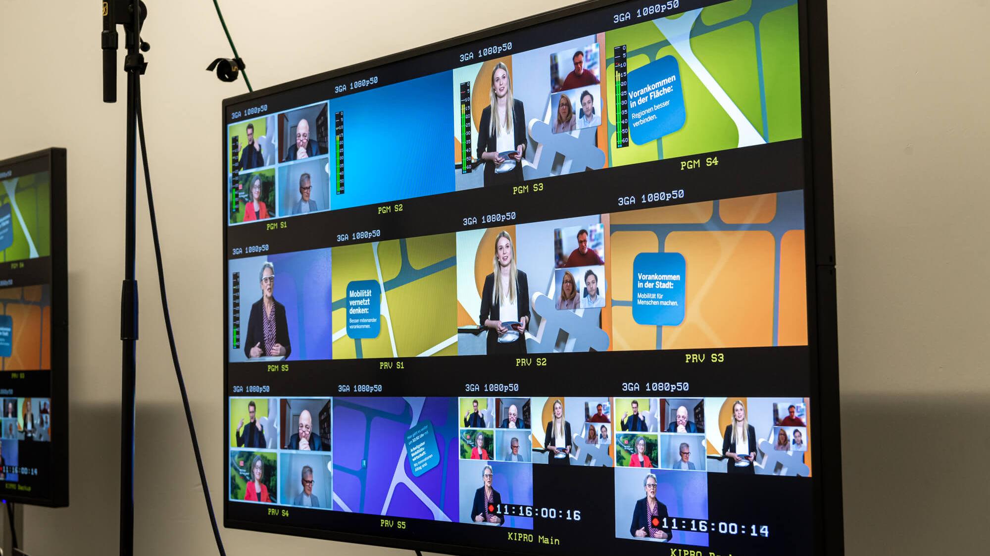 Großer Monitor, auf dem 12 kleinere Übertragungen einer TV-Aufzeichnung zu sehen sind.