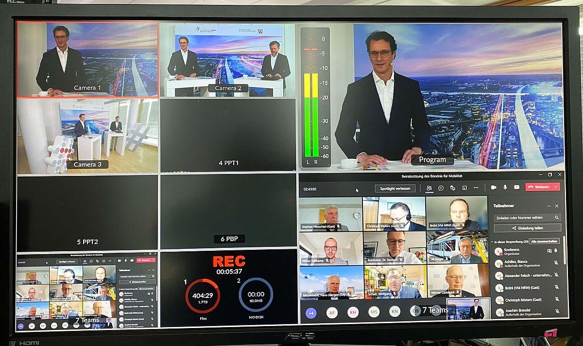 Ein großer Bildschirm zeigt mehrere Fenster, auf denen mehrere Menschen abgebildet sind, die eine Videokonferenz abhalten.