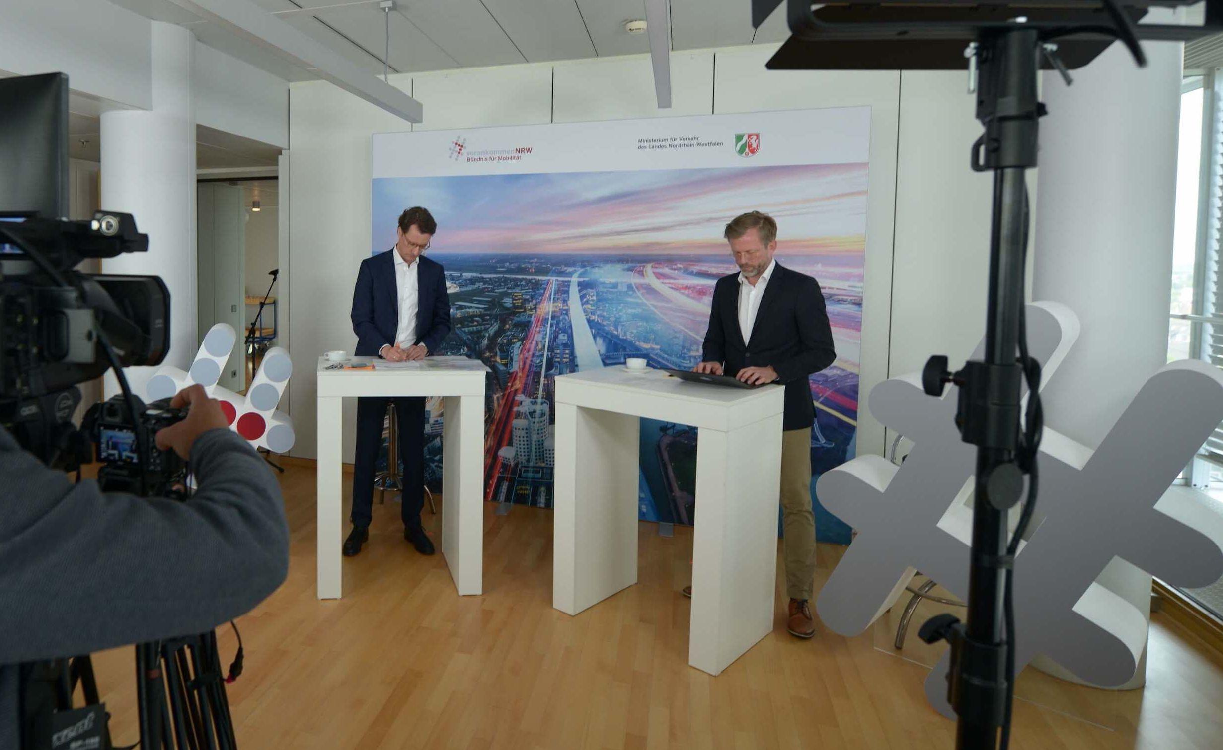 TV-Studio mit zwei Männern, die an zwei Pulten stehen und einem Kameramann.