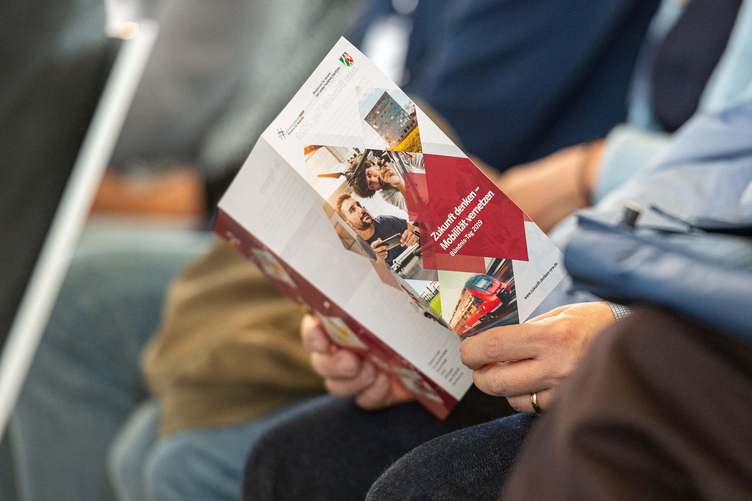 Teilansicht eines Menschen, der ene Broschüre zum Bündnis Tag liest.